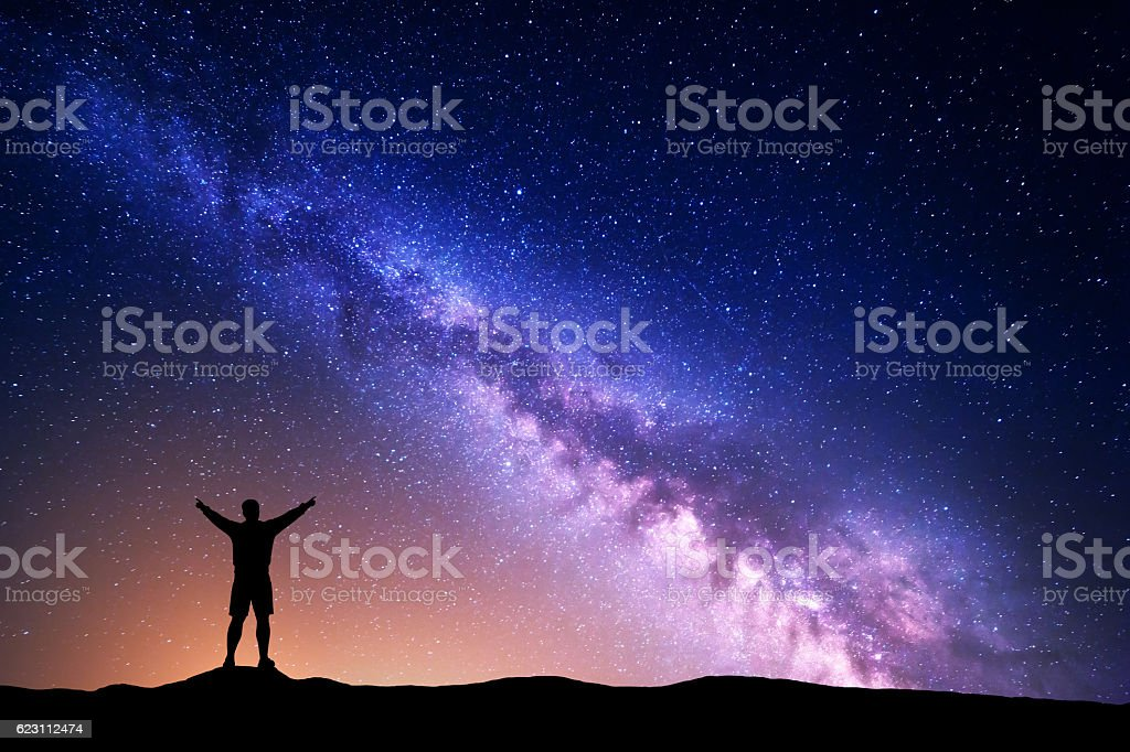 Purple Milky Way with silhouette of a standing man stock photo