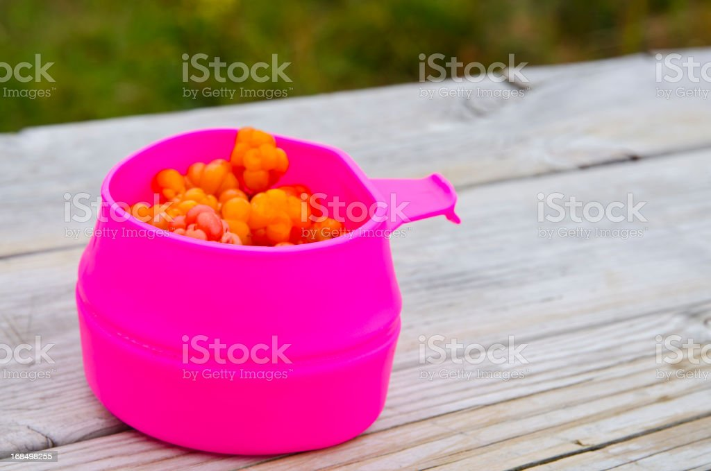 Purple mug with cloudberries on a wooden bench stock photo