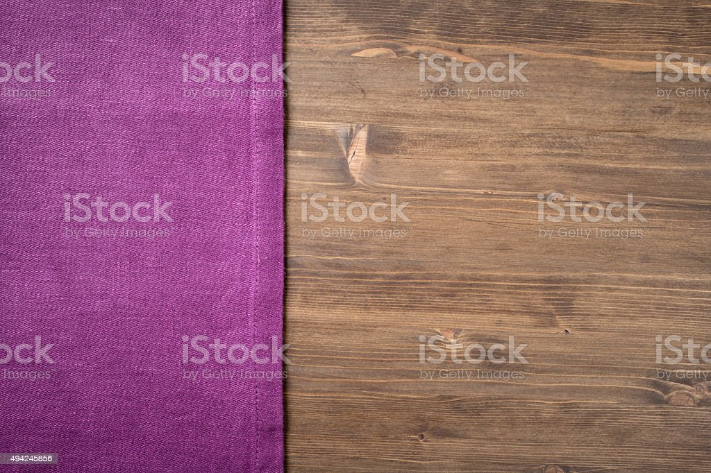 Purple  napkin from left side wooden table stock photo