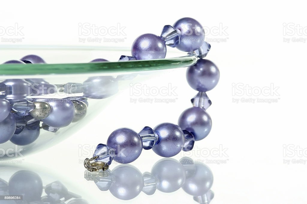 Purple necklace hanging from glass bowl royalty-free stock photo