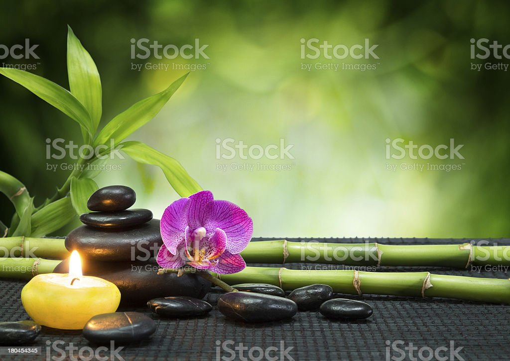 purple orchid, candle, with tower stones , bamboo on black mat stock photo