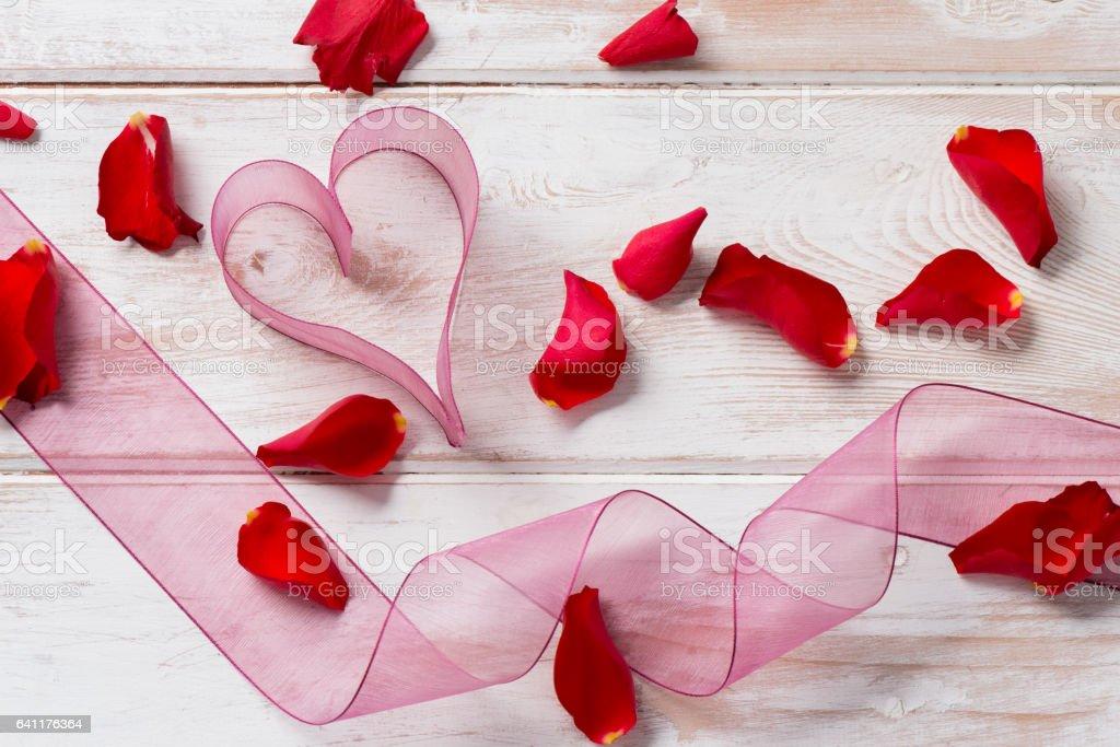 Purple Organza Ribbon Heart, Streamer, and Rose Petals stock photo