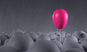Purple pink balloon rising from gray background: individuality, standing out