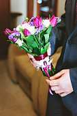 Purple, pink, white wedding bouquet  flowers in the hands of