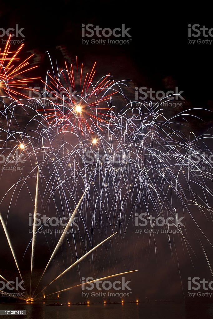 Purple, red and gold fireworks on the lake stock photo