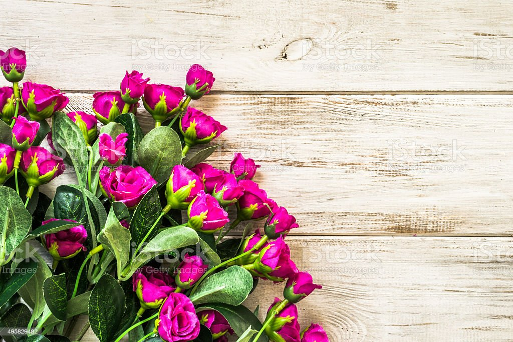 Purple roses flowers arranged on wood background. Flowers backgrounds. stock photo