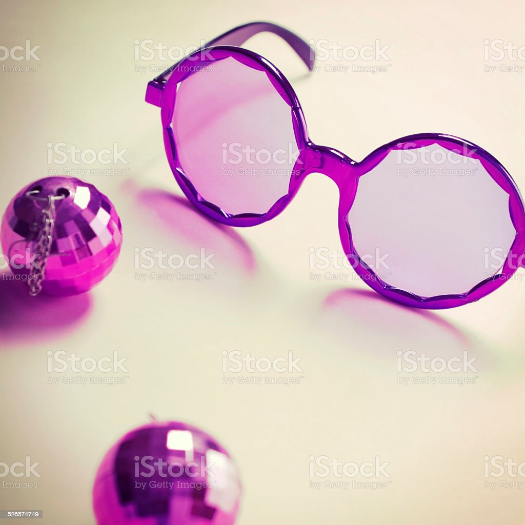 Purple sixties glasses with mini disco ball earrings stock photo
