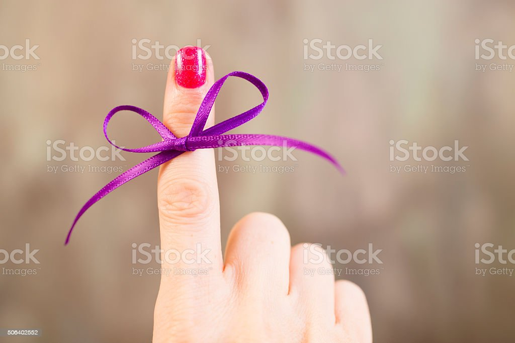 Purple social awareness ribbon tied around index finger. Reminder. stock photo
