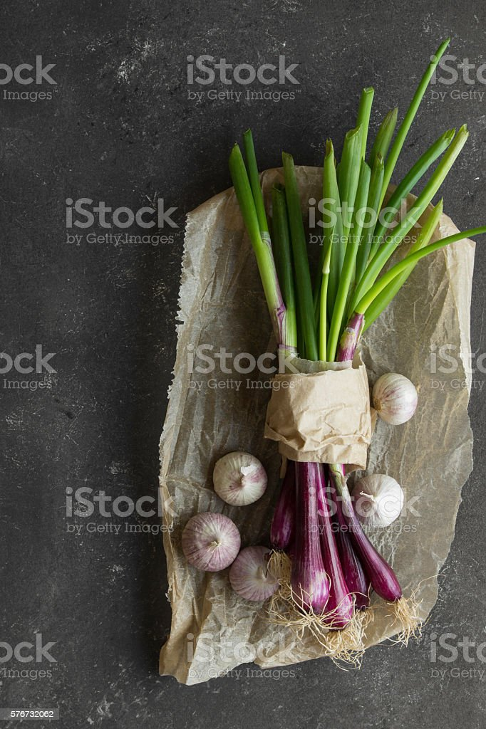 purple spring onions on dark table background stock photo