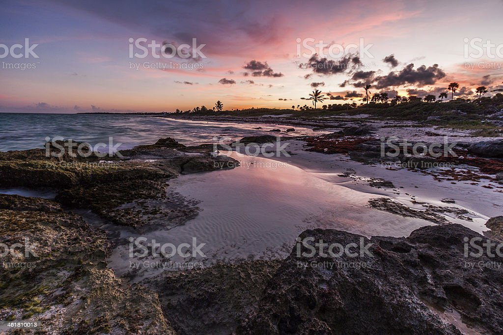 Purple sunset over a tropical rocky beach stock photo