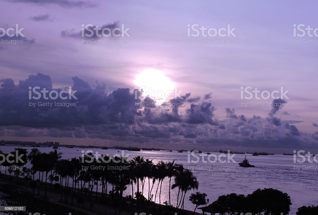 Purple sunset seascape with ships and clouds stock photo