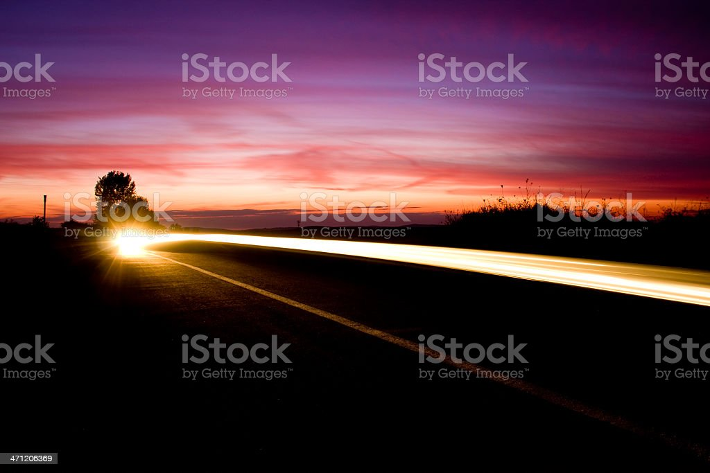 Purple sunset whit car headlights trail and copyspace royalty-free stock photo