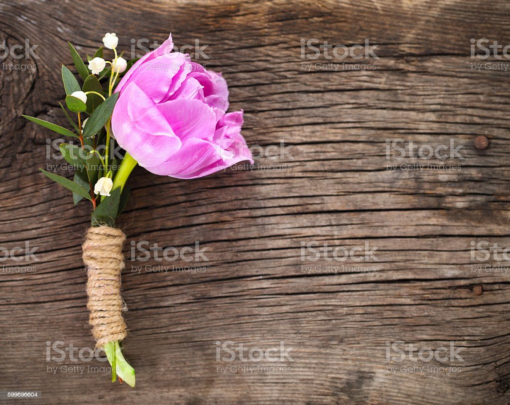 Purple tulip buttonhole for groom on the wooden background stock photo
