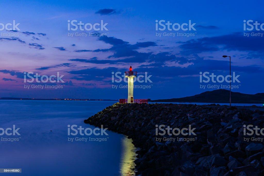Purple Twilight Ocean Reflection Lighthouse on Rocks Howth Ireland stock photo