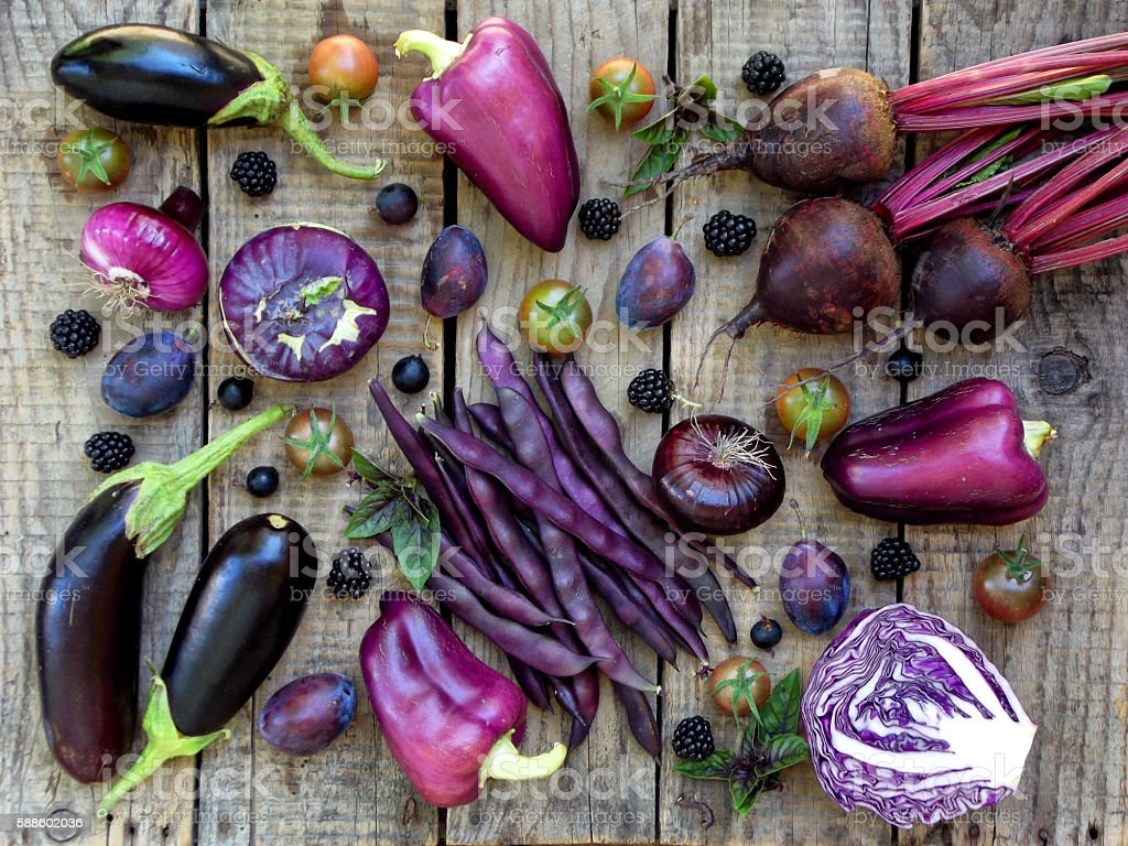 purple vegetables and fruits on wooden background stock photo