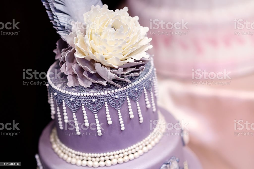 Purple wedding cake decorated with flowers stock photo