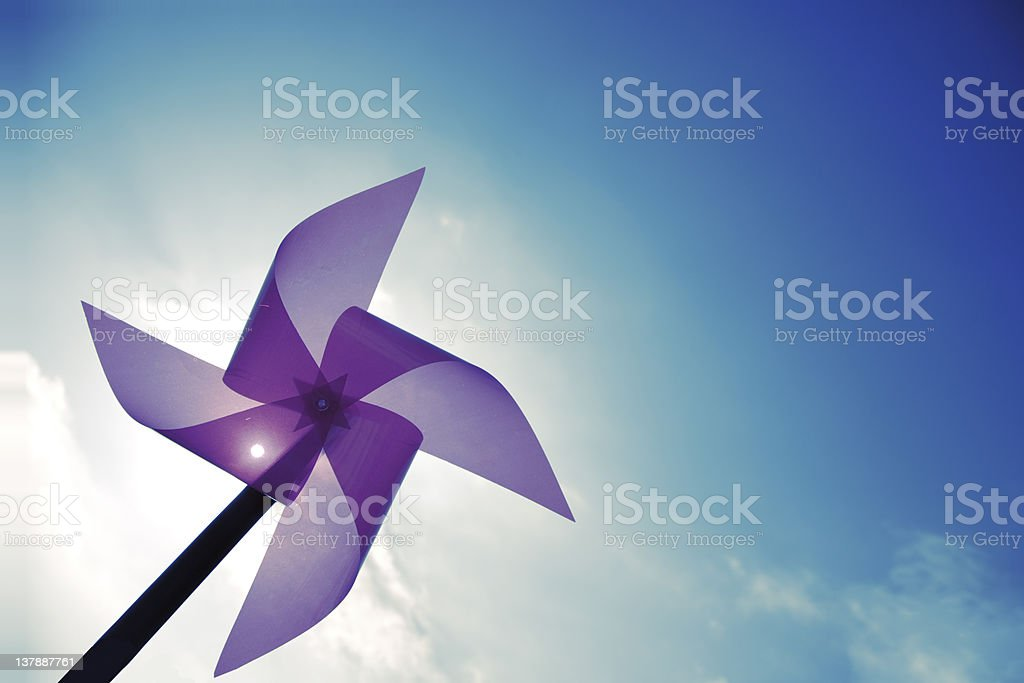 A purple windmill against a blue sky stock photo