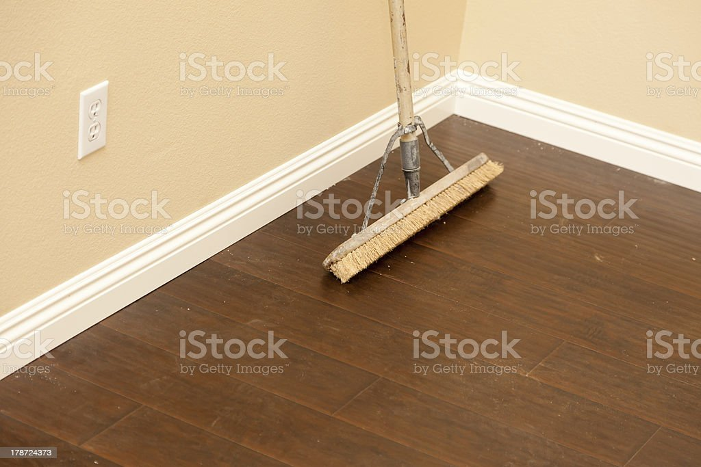 Push Broom on a Newly Installed Laminate Floor and Baseboard royalty-free stock photo