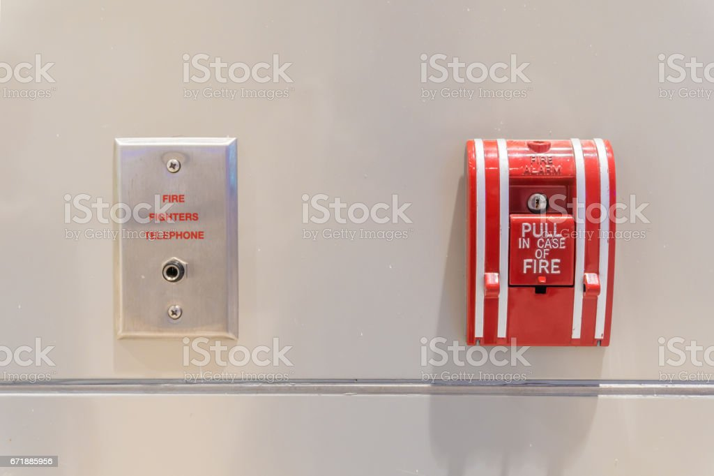 Push button switch fire alarm box on cement wall for warning and security system with fire fighters telephone port stock photo