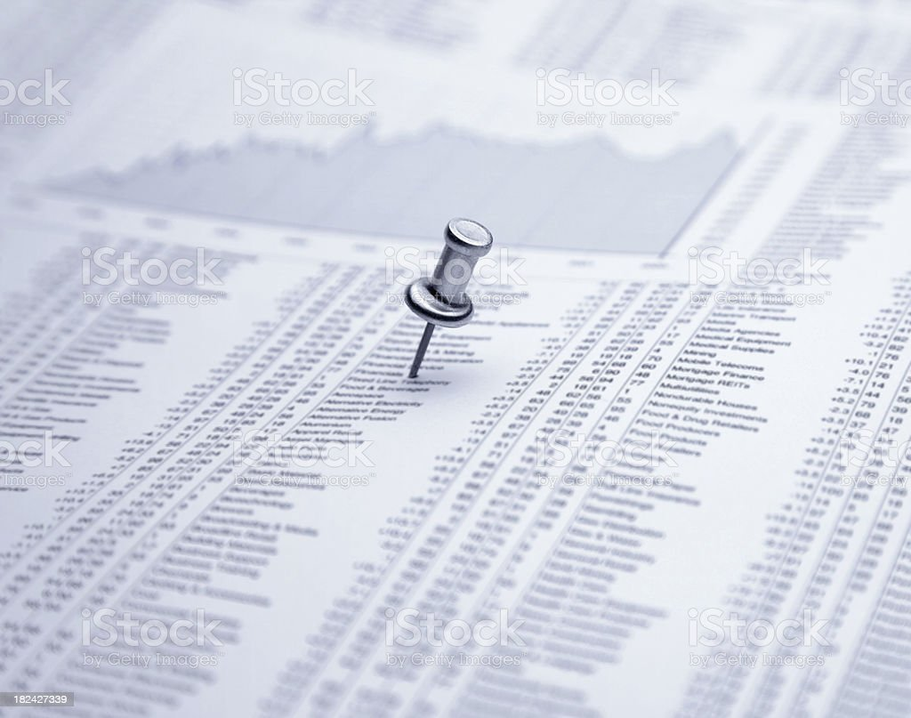 Push pin on financial newspaper stock photo