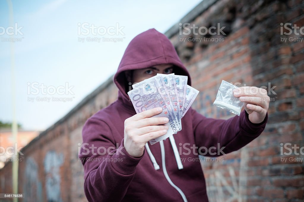 Pusher selling and trafficking drug dose for money cash stock photo