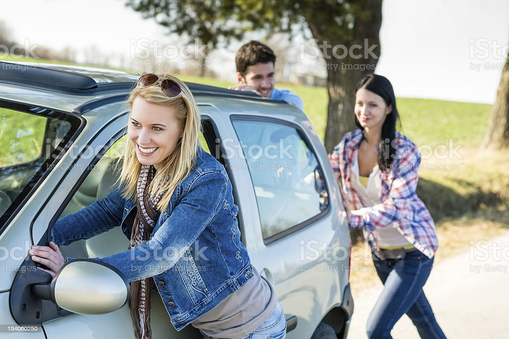 Pushing car technical failure young friends road stock photo