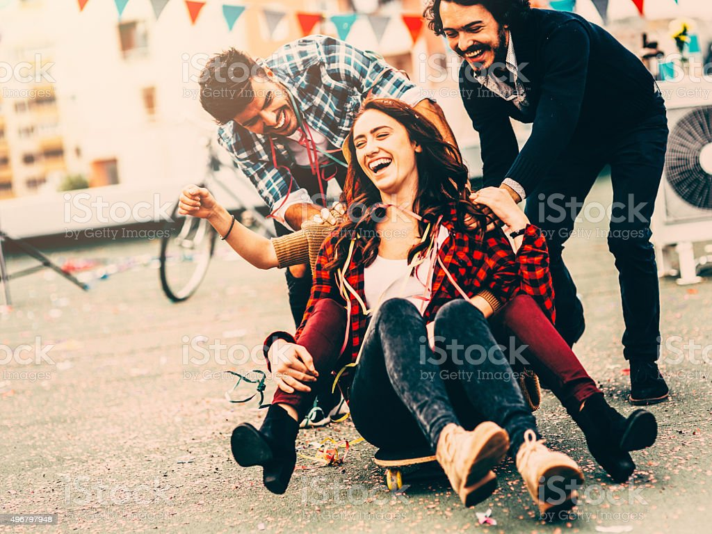Pushing friends on skateboard stock photo