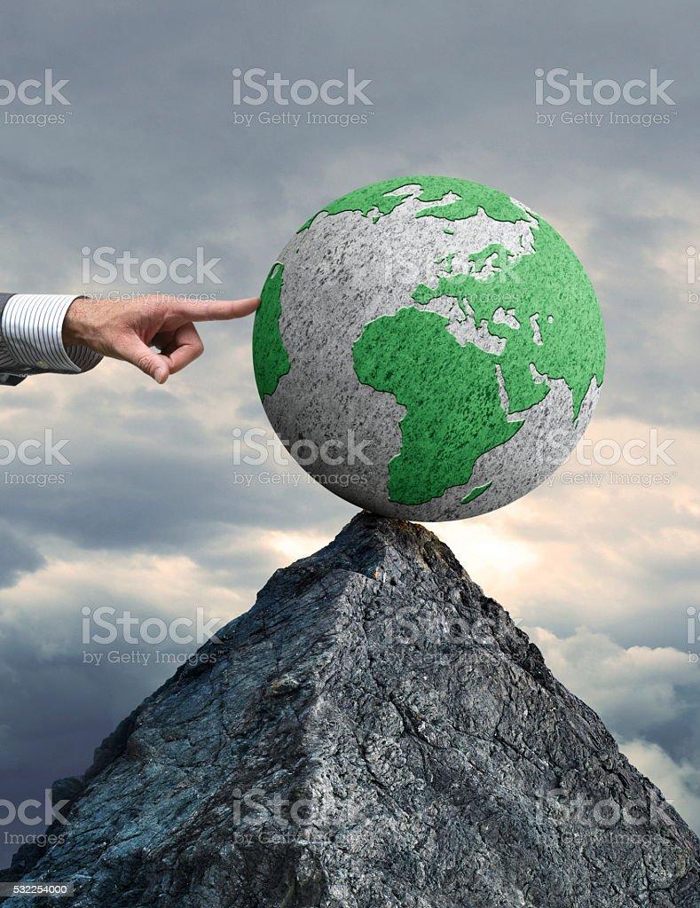 Pushing Globe Over The Edge stock photo