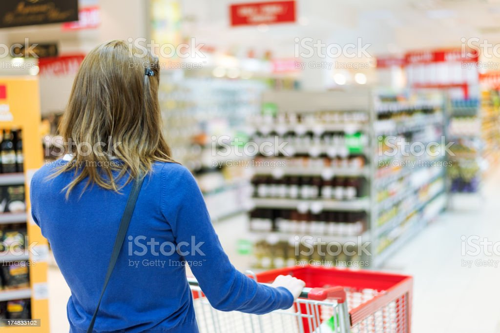 Pushing shopping cart in supermarket royalty-free stock photo