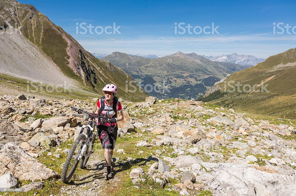 Pushing the bike uphill in Switzerland stock photo