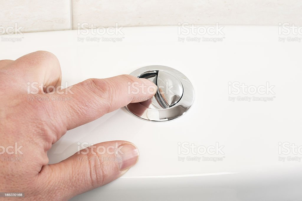 Pushing the flush button on a toilet stock photo