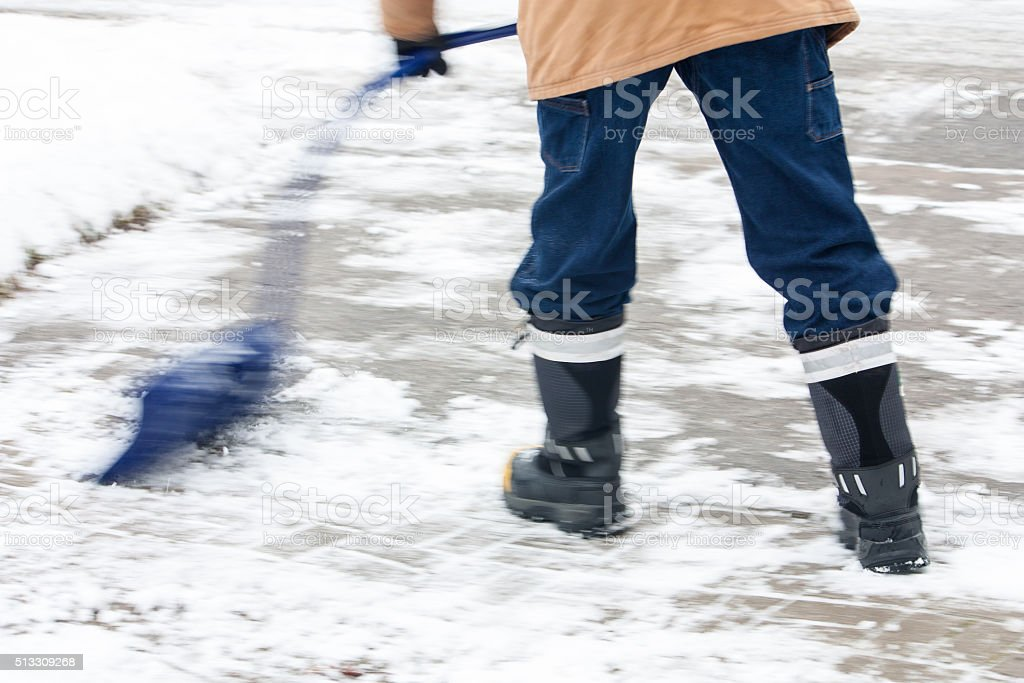 pushing the snow with curved snow shovel stock photo