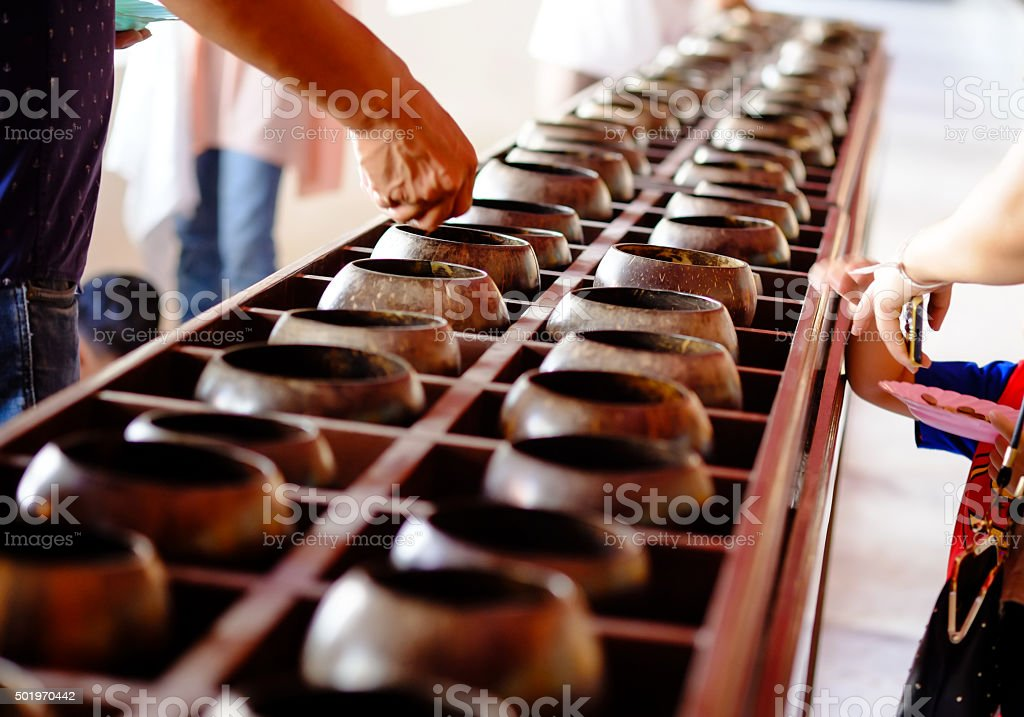 Put coin in Buddhist monk's alms bowl stock photo