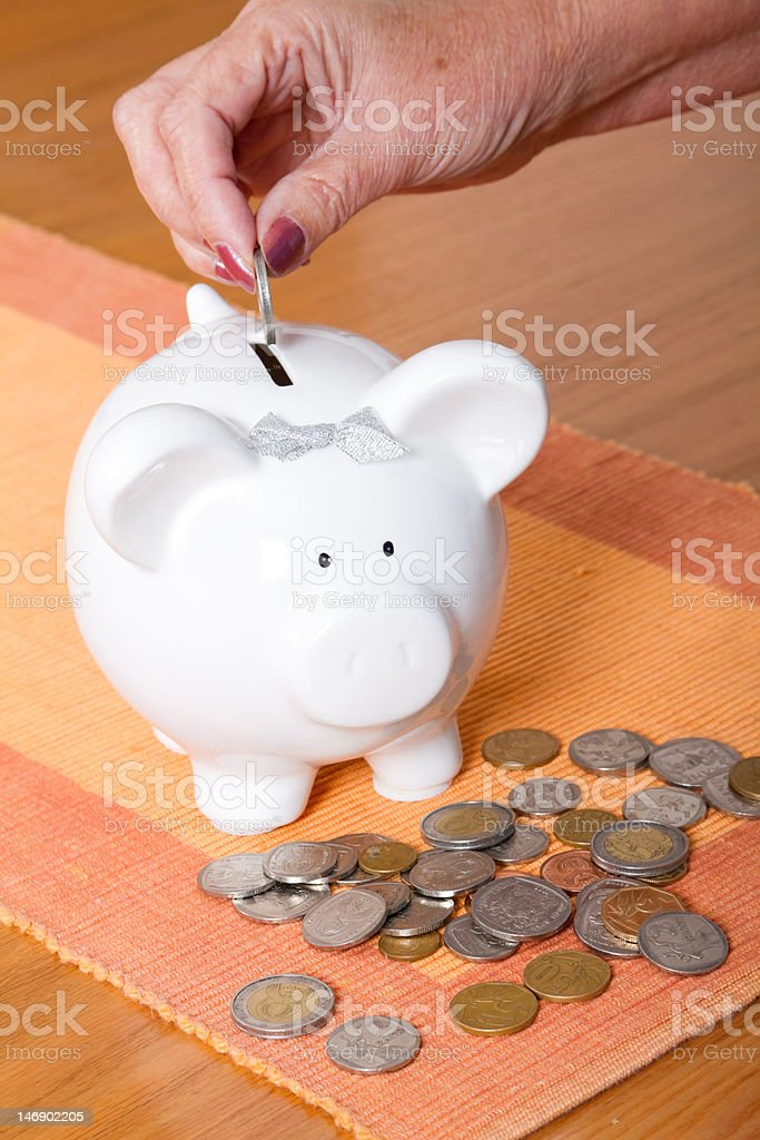 put coin in piggy bank royalty-free stock photo