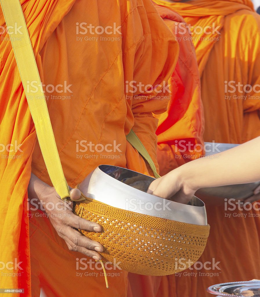 put food offerings in a Buddhist monk's alms bowl royalty-free stock photo