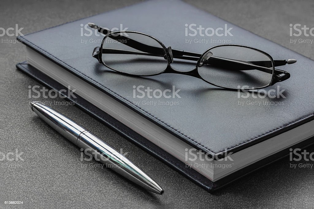 Put the glasses and pen on a notebook stock photo