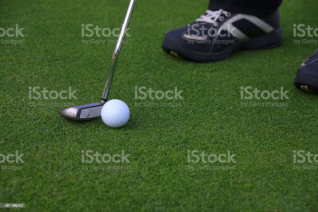 Putter and golf ball on grass prepare to putting
