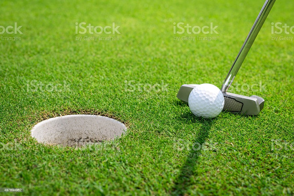 Putting a golf ball on the green stock photo