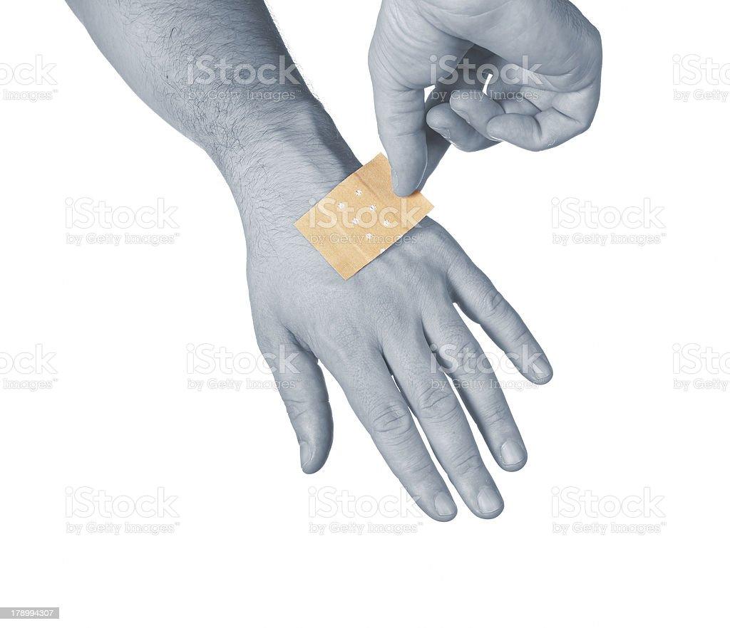 Putting a small adhesive bandage. stock photo