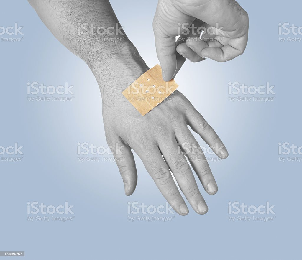 Putting a small adhesive stock photo