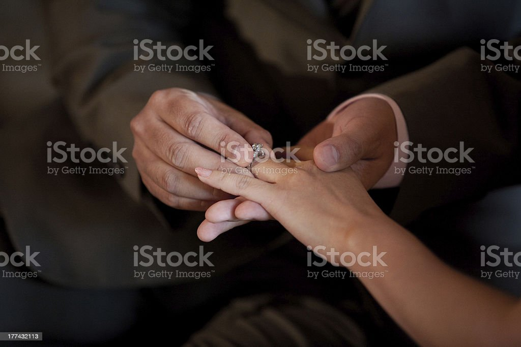 putting a wedding ring on the bride finger royalty-free stock photo