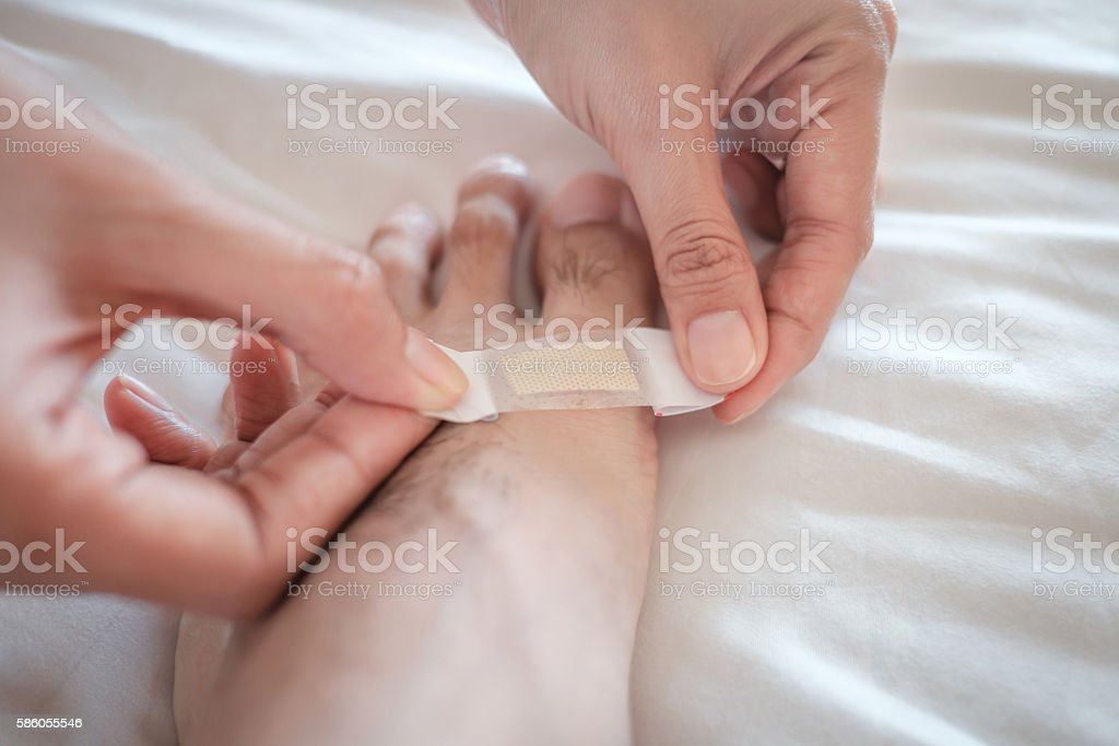 putting adhesive plaster on a leg, First aid kit. stock photo