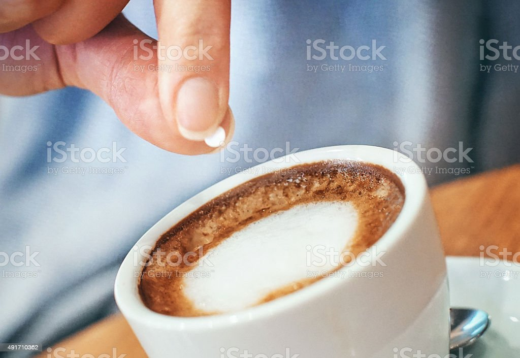 Putting artificial sweetener into coffee stock photo