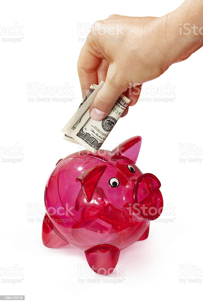 putting banknote into piggy bank royalty-free stock photo