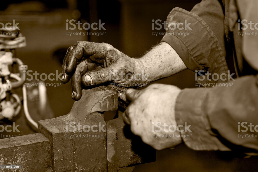 Putting car part into a vise, monochromatic, light sepia royalty-free stock photo