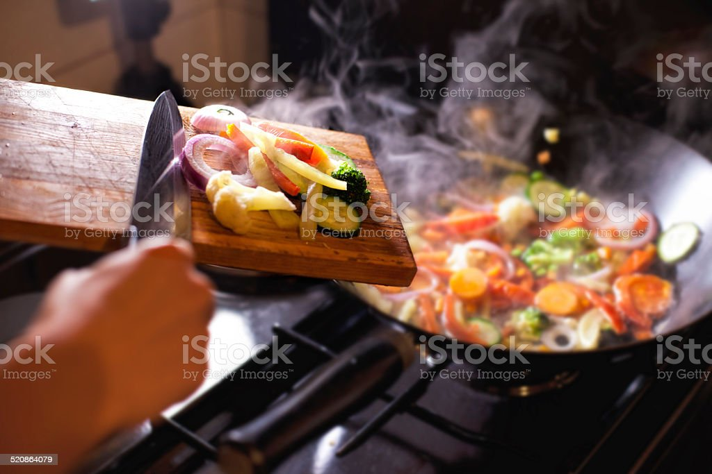 Putting chopped vegetables in the pan stock photo
