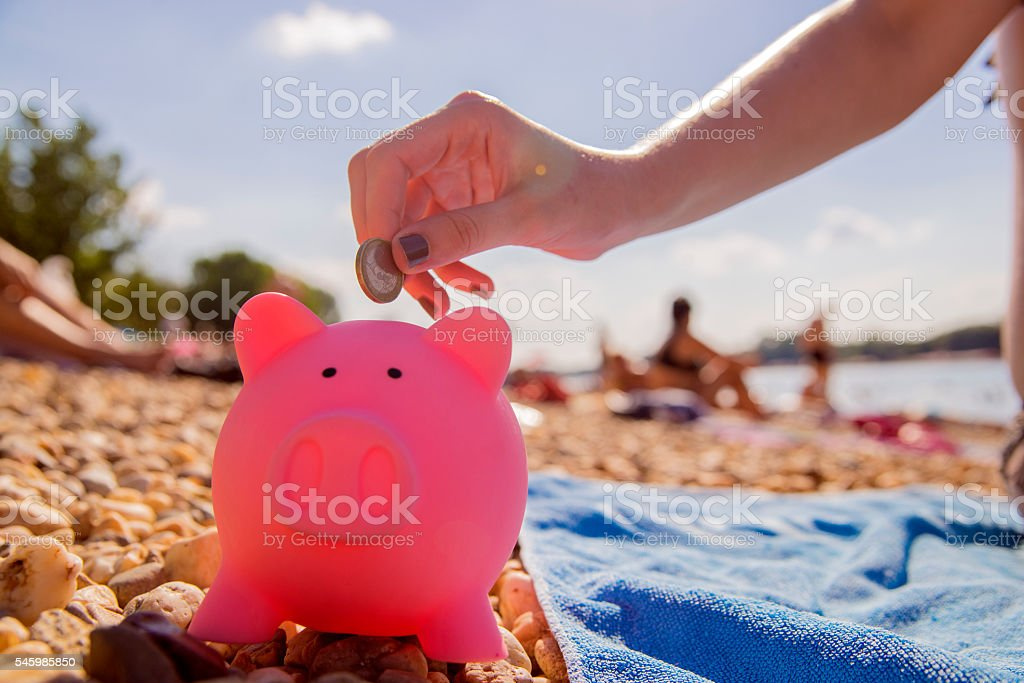 Putting coin into piggy bank - Holiday savings stock photo