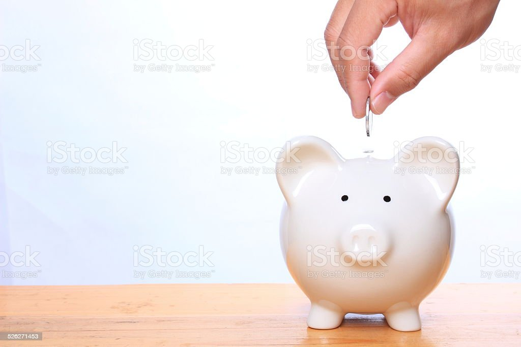 Putting coin into piggy bank stock photo