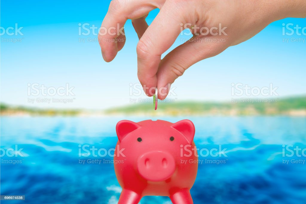 Putting coin into the piggy bank - Savings concept. Holiday. Travel. Stock Photo stock photo