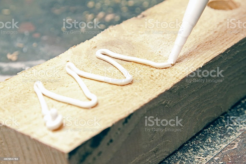 putting glue on a piece of wood stock photo